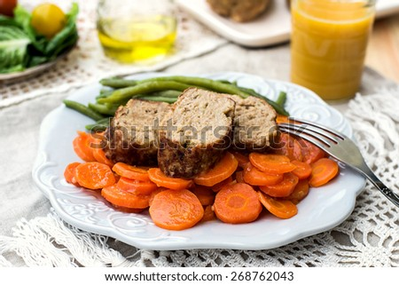 Italian veal meatloaf polpettone with carrots, green beans and sauce. Selective focus - stock photo