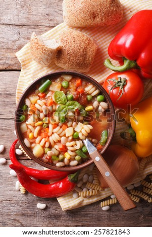 Italian vegetable minestrone soup in a bowl and ingredients on the table. vertical top view close-up  - stock photo