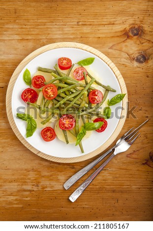 italian vegetable salad with boiled potato, cherry tomatoes, green beans, olive oil & beef steak. served with white wine. on wooden background  - stock photo