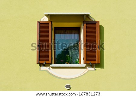 Italian Window with Open Wooden Shutters, Decorated With Fresh Flowers - stock photo