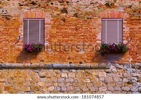 Italian Windows with Closed Shutters, Decorated with Fresh Flowers - stock photo