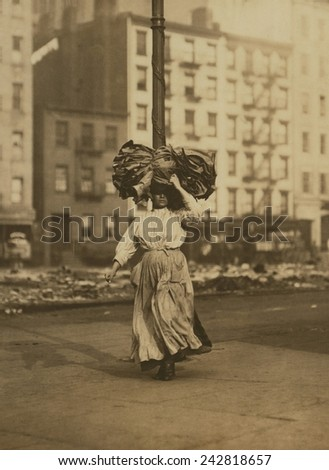 Italian woman carrying heavy bundle of clothing on her head Near Astor Place, New York City. She will sew the garments at home for low wages. February 1912 photograph by Lewis Hine. - stock photo