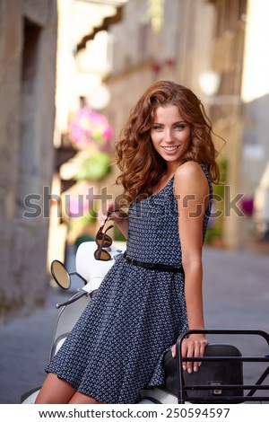 Italian woman on a scooter on the streets of the Tuscan town.  - stock photo