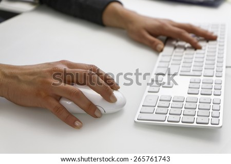 Italy, female hands on a computer mouse and keyboard - stock photo