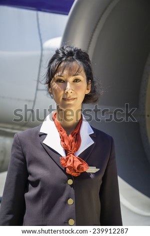 Italy, flight stewardess near an airplane - stock photo