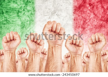 Italy Labor movement, workers union strike concept with male fists raised in the air fighting for their rights, Italian national flag in out of focus background. - stock photo