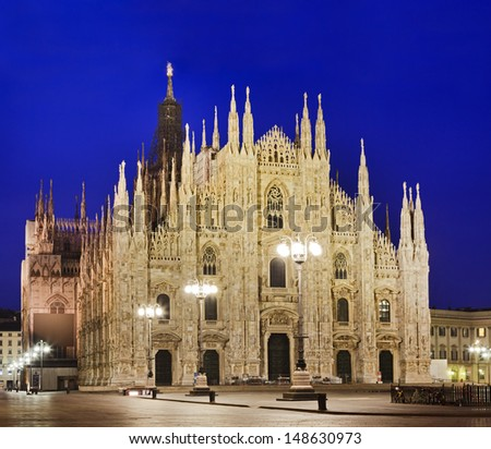 Italy Lombardy capital Milan central square and Cathedral gothic religious church facade at sunrise illuminated decorated walls, doors and towers - stock photo
