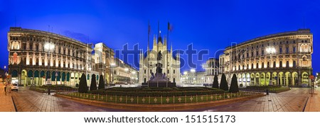 Italy MIlan central square panoramic view end to end with cathedral in the middle facade and wings of baroque buildings cityscape landmark at sunrise under blue sky with illuminated lights - stock photo