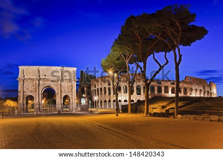 Italy Rome capital of ancient civilization coliseum and arch of Constantine at sunrise illuminated with trees as famous landmarks - stock photo