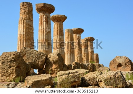 Italy, Sicily island, the site of temples valley is classified to the world heritage of UNESCO. The Heracles temple is one of the oldest. There are only 8 columns up, but its footprint is impressive. - stock photo