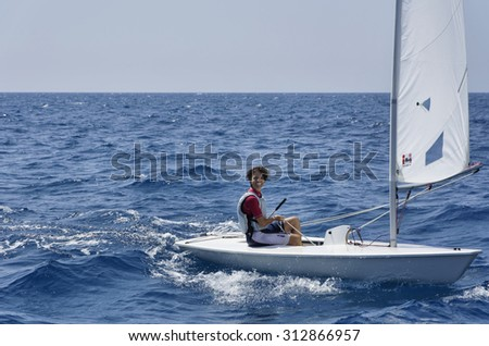 Italy, Sicily, Mediterranean Sea; 28 august 2015, woman sailing on a small sailing boat - EDITORIAL - stock photo