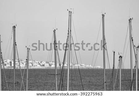 Italy, Sicily, Mediterranean sea, Marina di Ragusa, sailing boat  masts in the marina and the sicilian coastline in the background - stock photo