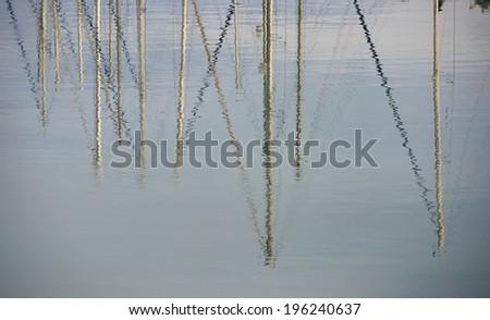 Italy, Sicily, Mediterranean sea, Marina di Ragusa, sailing boat  masts reflected in the water - stock photo