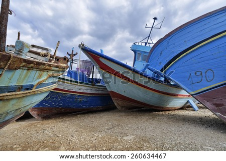 Italy, Sicily, Portopalo di Capo Passero, old libyan wooden fishing boats ashore - stock photo