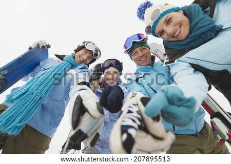 Italy, South Tyrol, Four people in winter clothes, smiling, low angle view - stock photo