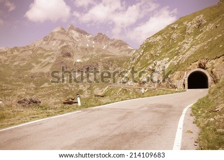 Italy, Stelvio National Park. Famous road to Gavia Pass in Ortler Alps. Alpine landscape. Cross processing color style - retro filtered tone. - stock photo
