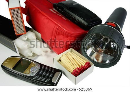 Items for emergency or power outage kit - mobile phone, candles, matches, torch, first aid, battery radio - stock photo