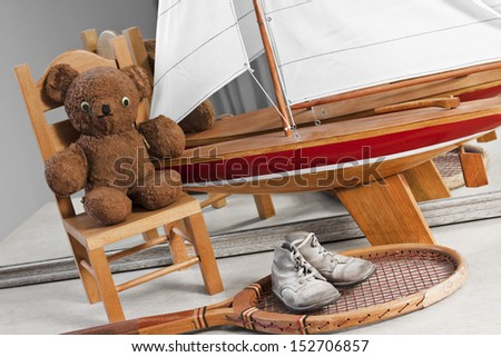 items from childhood through youth that include baby shoes, teddy, and little chair, sailboat, and tennis racket.  - stock photo
