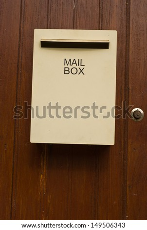 Ivory colour mailbox with the wood door - stock photo