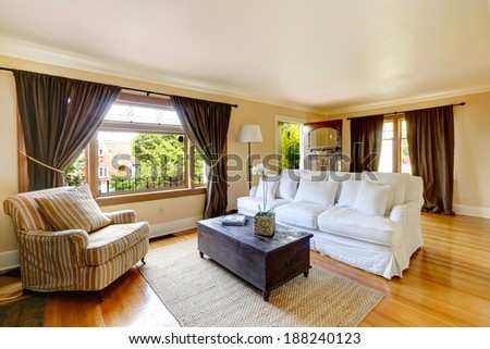 Ivory living room with curtained windows, hardwood floor. Room furnished with white comfortable sofa, antique chest and striped old armchair. View of open entrance door - stock photo