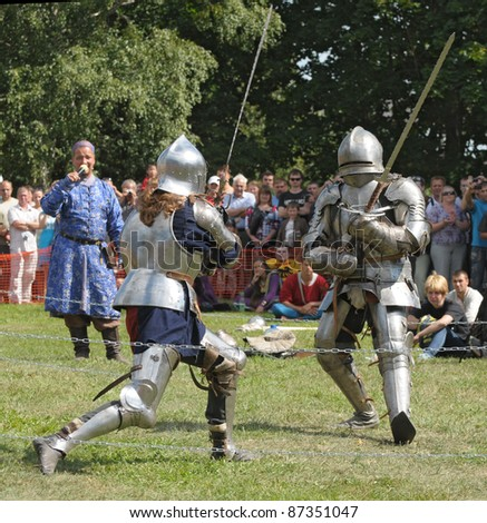 "IZBORSK, RUSSIA - AUGUST 6: Unidentified ean in a knightly armor take part in festival ""Iron hailstones"" on August, 6 2011 in Izborsk, the Pskov area, Russia. - stock photo"