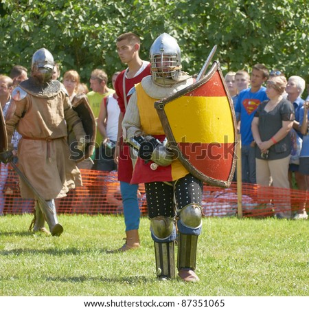 "IZBORSK, RUSSIA - AUGUST 6: Unidentified man in a knightly armor takes part in festival ""Iron hailstones"" on August, 6 2011 in Izborsk, the Pskov area, Russia. - stock photo"
