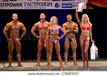 Izhevsk, Russia - April 18, 2015. Open championship of the Volga Federal District of bodybuilding and fitness bikini. On stage, the winners of the competition in bodybuilding and fitness bikini - stock photo