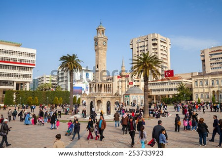Izmir, Turkey - February 5, 2015: Konak Square with crowd of tourists walking near the historical clock tower, symbol of Izmir City - stock photo