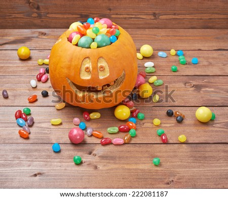 Jack o lantern halloween pumpkin filled with multiple colorful sweets and candies over the wooden board background composition - stock photo