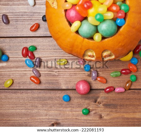 Jack o lantern halloween pumpkin filled with multiple colorful sweets and candies over the wooden board background composition, top view above foreshortening - stock photo