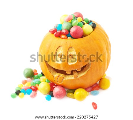 Jack o lantern Halloween pumpkin with the smiling face and filled with multiple colorful sweets and candies, composition isolated over the white background - stock photo