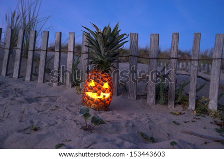 Jack o lantern made out of pineapple glowing at dark on beach - stock photo