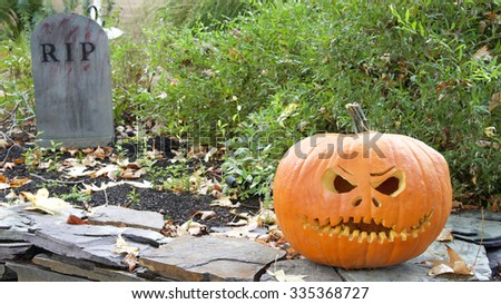 Jack o Lantern outside in daylight among fallen leaves with RIP sign in the background. Remnants of Halloween.  - stock photo