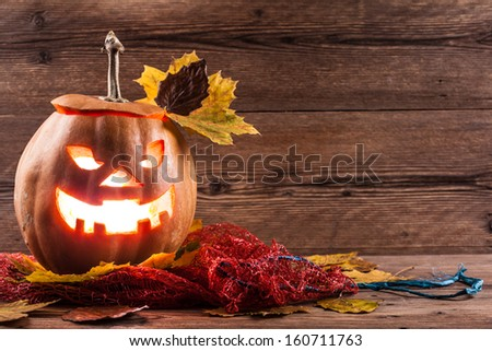 jack-o-lantern with leaves on wooden background - stock photo