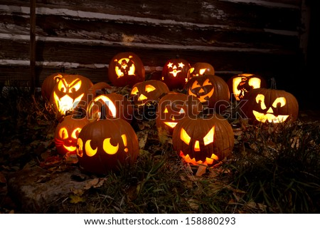 Jack-O-Lanterns Carved for Halloween Lit in Orange in Grass With Fallen Leaves By a Barn - stock photo