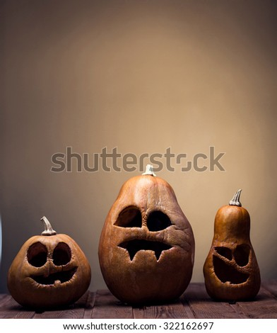 Jack o lanterns Halloween pumpkin face on wooden background and autumn leafs - stock photo