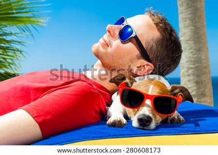 jack russell dog  and owner sunbathing a having a siesta under a palm tree , on summer vacation holidays at the beach - stock photo