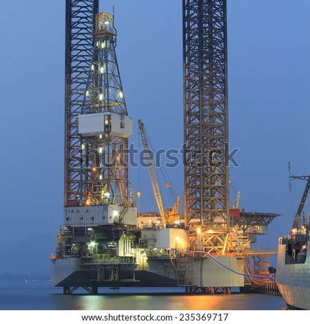 Jack up oil drilling rig in the shipyard in the evening - stock photo