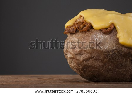 Jacket of potato with pulled pork and cheese on top shot on a wooden background - stock photo