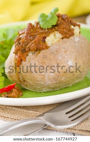 Jacket Potato - Baked potato topped with chilli con carne. - stock photo