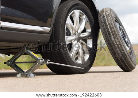 Jacking up a car to change a tyre after a roadside puncture with the hydraulic jack inserted under the bodywork raising the vehicle and the spare wheel balanced on the side - stock photo