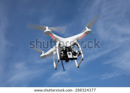 JACKSONVILLE, FL. USA - JUNE 14, 2015: A DJI Phantom consumer drone flying in the sky with a GoPro Hero 3 action camera. The global market for consumer drones is forecast to top $300 million by 2018. - stock photo