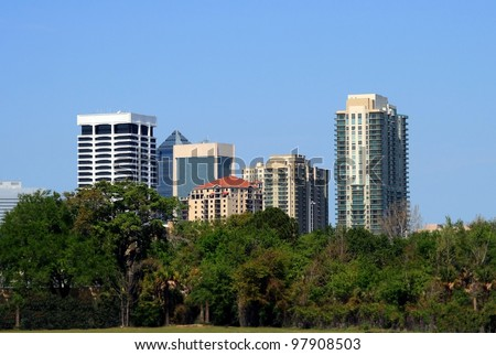 Jacksonville Florida highrise as seen through treeline - stock photo