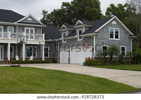 Jacksonville Florida, USA - MAY 04, 2016: American flag, Garage door and Basketball hoop in style home in residential neighborhood USA. area near Jacksonville beach. - stock photo