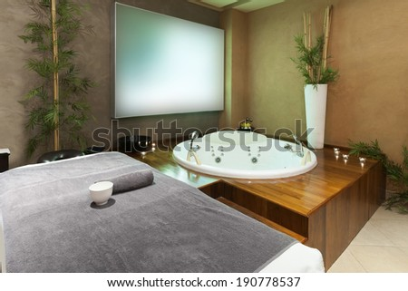 Jacuzzi bath and massage table in hotel spa center - stock photo
