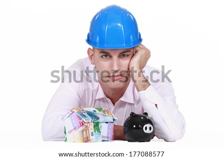 Jaded man posing with a piggy bank and a house made of money - stock photo