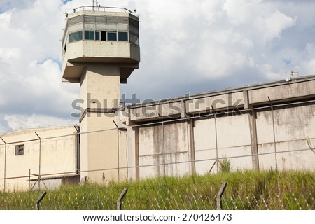 Jail tower and walls surrounded by wires - stock photo