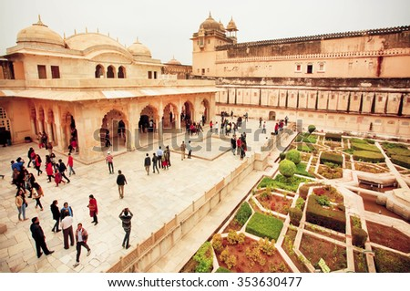 JAIPUR, INDIA - JAN 23: Many people in garden of the Amber Fort with historical stone palaces on January 23, 2015 in Rajasthan. Amber Fort was built in 1592 by rajput Raja Man Singh. - stock photo