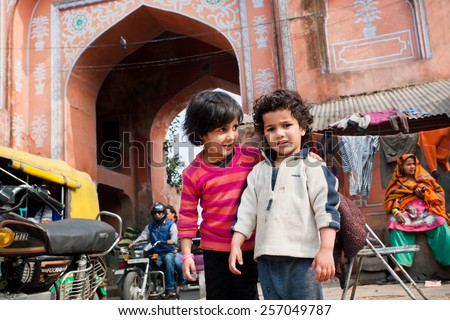 JAIPUR, INDIA - JAN 25: Unidentified children play outdoor on the full of traffic street in Pink City on January 25, 2015. Jaipur, with population 6,664000 people, is a capital of Rajasthan - stock photo