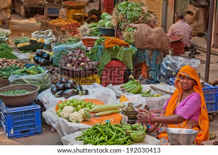 JAIPUR, INDIA - MARCH 26, 2014: An unidentified trader awaiting custom in the fruit and vegetable market in the old Johari Bazaar district of the city - stock photo